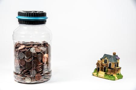 Krug voller Münzen bei einem Miniaturhaus, das Geldsparen für eine Hypothek darstellt