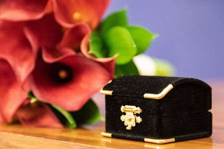 Box containing wedding rings before the ceremony by a red flower bouquet 写真素材