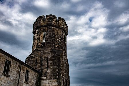 Vigilance structure of an abandoned jail on a cloudy day Stock Photo