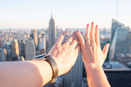 Newly wed couple showing their hands with rings in Manhattan