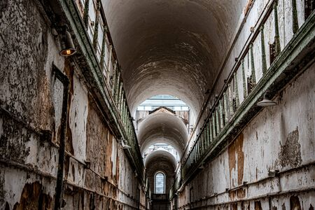 One of the wings of an abandoned penitentiary with the entrance to small cells on both sides