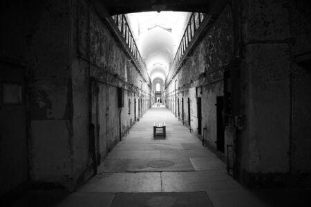 Una de las alas de una penitenciaría abandonada con entrada a pequeñas celdas a ambos lados Foto de archivo
