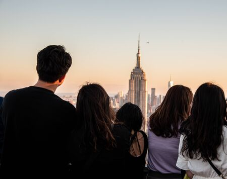 Tourists looking at the Empire State one of the most iconic buildings in NYC Stock Photo