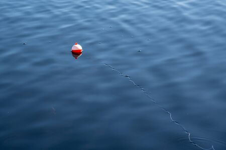 Orange and white buoy in a lake in Canada
