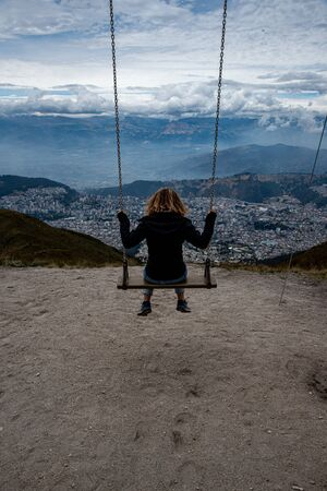Pincture of a woman on a swing on top of the Pichincha volcano in Quito (Ecuador)