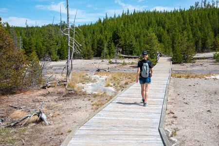 Boardwalk with a woman at Norris geyser basin in Yellowstone
