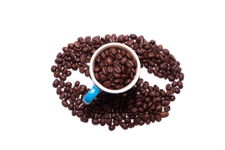 Coffee bean shape created with coffee beans and a coffee mug filled with coffee beans over a white background
