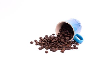 Coffee beans spilled from a mug isolated over a white background Фото со стока