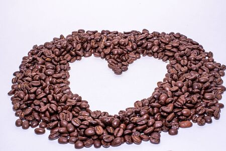 Heart frame formed by coffee beans over a white background Reklamní fotografie