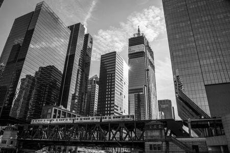 Subway train over the Chicago river with skyscrapers on the background