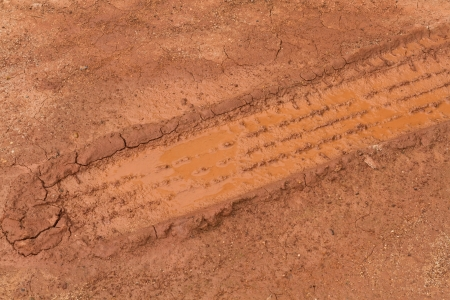 tire tracks deep in mud, dry dirt, and dust running at a angle photo