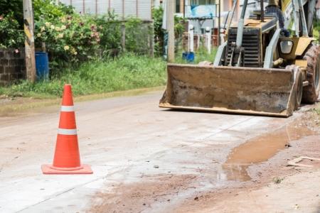 redirect: bulldozer performing road construction with orange cones.