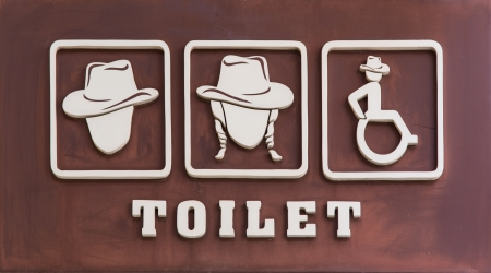 stating: A carved wooden sign stating Toilets  toilets  in Thailand