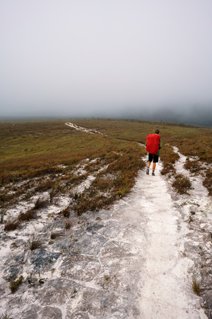 A man hiking on a path with fog in the sky