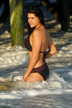 woman kneeling: Beautiful, sexy, young hispanic woman kneeling in the surf,