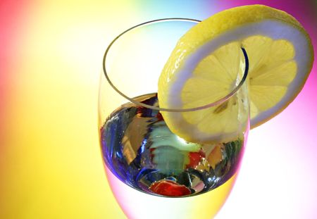 Glass of champagne with a cherry and a lemon