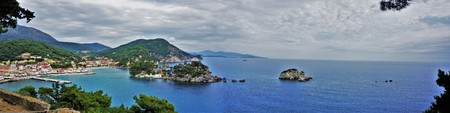 Look at the town of Parga, the Bay and the island of Panagia. A combination between mountain and sea, cottages in old and new Mediterranean style. One of the most mysterious and magical places in Greece. Foto de archivo - 96125697