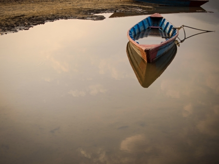 Single rowing boat marooned, anchored, floating on the still waters of a lake