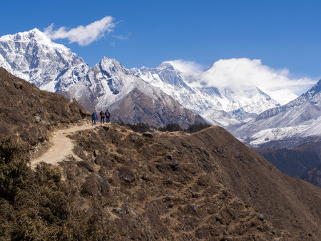 Trekkers walking on the trail to Everest Base Camp with Mount Everest in the background  photo