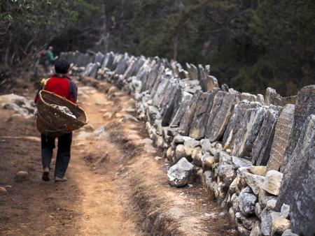 Sherpa porter walking on trail next to Tibetan mani stones  Stock Photo