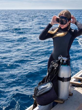 スキューバ ダイビングのための準備でボートに乗って美しい女性ダイバー