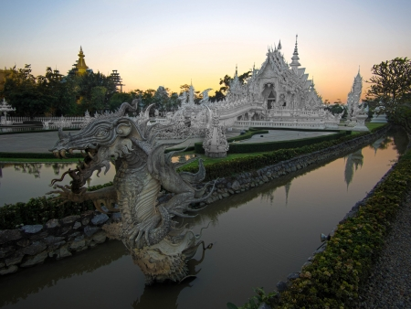 popularly: Wat Rong Khun, popularly known as the White Temple, at sunset in Chiang Rai, Thailand