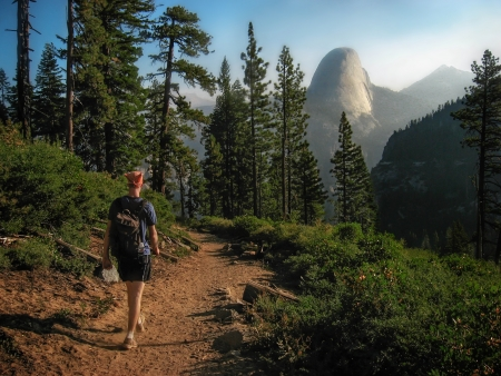 Hiker walking on trail towards the Half Dome in Yosemite National Park, California