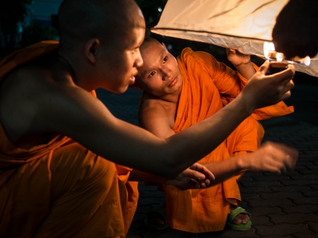 Buddhist Monks Lighting Up Hot Air Balloon at Loi Krathong 2013 Festival