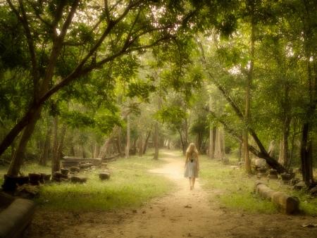 魅惑の森の神秘的なパスで裸足で歩く若い女性 写真素材