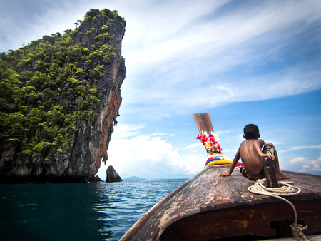 Boy on Longtail Boat in Ko Phi Phi, Thailand photo