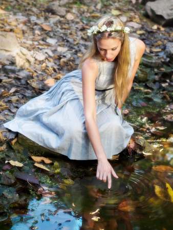Beautiful Fairytale Princess Sitting By Water Pond and Touching Her Reflection in the Water