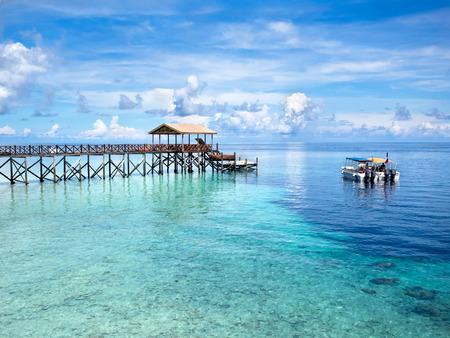 the sky clear: Barcos en el sitio de buceo frente a la costa de la isla de Pulau Sipadan, Sabah, Malasia Oriental Foto de archivo