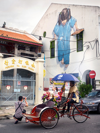 cartoon window: Tourists in Front of Famous Street Art Mural in Georgetown, Penang, Malaysia