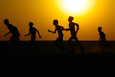 暖かい日の出の空に対してフィールドを走っている少年たちのシルエット