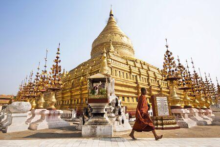 buddhist structures: Buddhist Monk Walking Around Sacred Shwezigon Pagoda in Bagan, Myanmar (Burma)