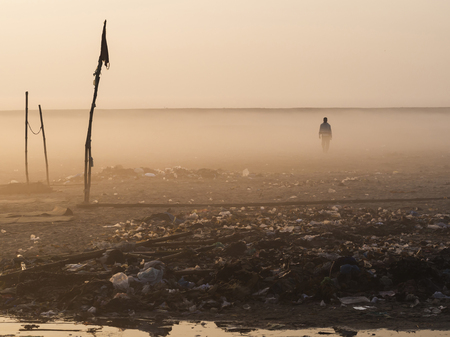 Man walking on dusty, littered landscape East of the Ganges river in Varanasi, Uttar Pradesh, India.