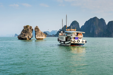Tourist boat visiting the Kissing Rocks in Halong Bay, North Vietnam