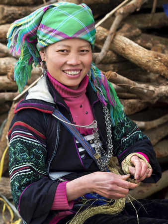 Happy Hmong woman smiling, dressed in traditional attire in Sapa, Vietnam