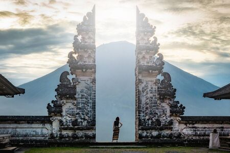 Female traveller standing at the ancient gates of Pura Luhur Lempuyang temple in Bali, Indonesia.