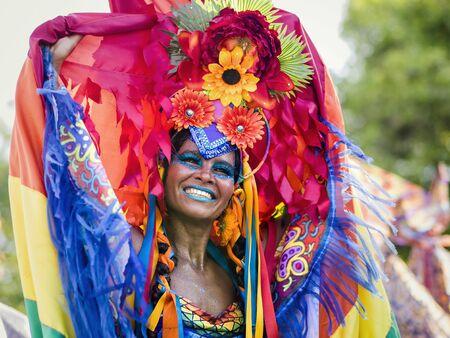 Rio de Janeiro, Brazil - February 9, 2016: Beautiful Brazilian woman of African descent wearing colourful costume and smiling during Carnaval 2016 street parade in Rio de Janeiro, Brazil. Редакционное
