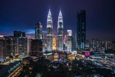 Kuala Lumpur City Centre aka KLCC complex including national landmark Petronas Twin Towers illuminated at night in Kuala Lumpur, Malaysia.