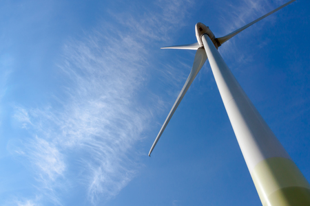 A wind turbine against blue sky and white cloud Stock Photo