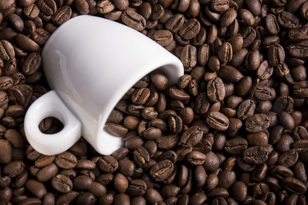 decaffeinated: A lots of roasted coffee beans with a espresso cup Stock Photo