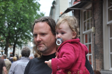 Breda, Netherlands, August 15, 2010, Harleyday,  Man with daughter on his arm between the audience at Harleyday in Breda (2010)