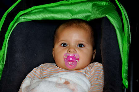 Made, Noord-Brabant, Netherlands - September 26, 2010 - Colorful fair in a small Dutch village, a young baby girl in the baby carriage  Stock Photo - 8739142