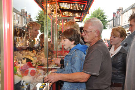 made in netherlands: Made, Noord-Brabant, Netherlands - September 26, 2010 - Colorful fair in a small Dutch village,t he father helps his son with the machine  Editorial