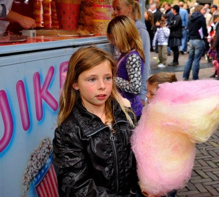 made in netherlands: Made, Noord-Brabant, Netherlands - September 26, 2010 - Colorful fair in a small Dutch village, a young girl with her cotton candy Editorial