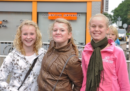 noord: Made, Noord-Brabant, Netherlands - September 26, 2010 - Colorful fair in a small Dutch village, three smiling young girls in a row Editorial