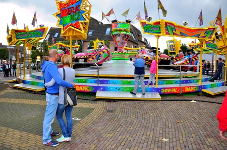 made in netherlands: Made, Noord-Brabant, Netherlands - September 26, 2010 - Colorful fair in a small Dutch village, young couple arm in arm watching a fairground attraction