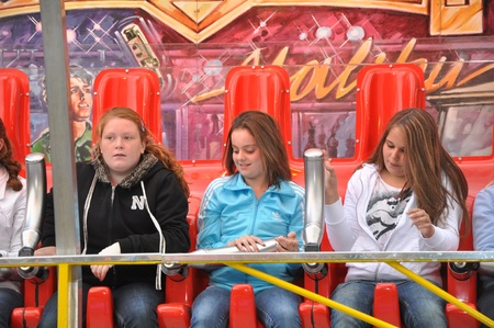 made in netherlands: Made, Noord-Brabant, Netherlands - September 26, 2010 - Colorful fair in a small Dutch village, three young girls in a fairground attraction